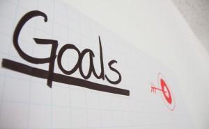 """Flipchart-Darstellung des Wortes """"Goal"""" (Ziel) mit einer stilisierten Dartscheibe"""